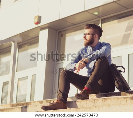 Confident businessman with arms crossed next to his office building - stock photo