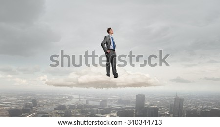 Confident businessman with arms on waist standing on cloud