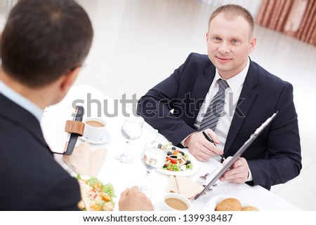 Confident businessman with clipboard looking at camera during paper discussion at business lunch