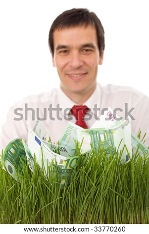 Confident businessman with euro banknotes in grass - focus on money, green business concept - stock photo