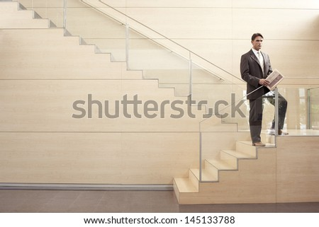 Confident businessman with newspaper looking away while standing on steps in office