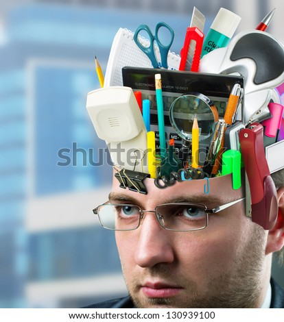 Confident businessman with office accessories in head - stock photo