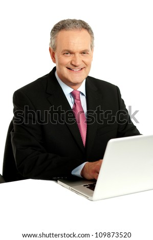 Confident businessman working on laptop isolated over white background - stock photo