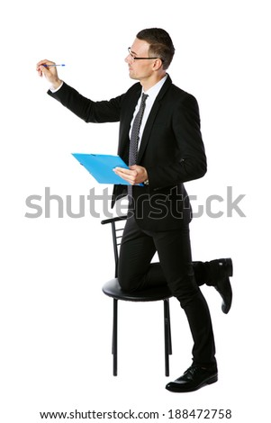 Confident businessman writes with pen at copyspace over white background - stock photo