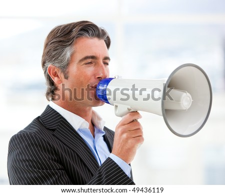 Confident businessman yelling through a megaphone in the office - stock photo