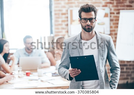 Confident businessman. Young handsome man holding notepad and looking at camera while his colleagues discussing something in the background  - stock photo