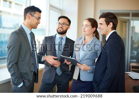 Confident businesspeople listening to their partner explaining his idea - stock photo