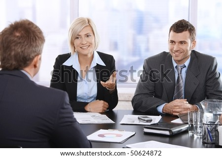 Confident businesspeople smiling at meeting table in office.