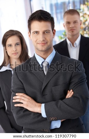 Confident businessteam, focus on smiling elegant businessman standing with arms crossed, looking at camera. - stock photo