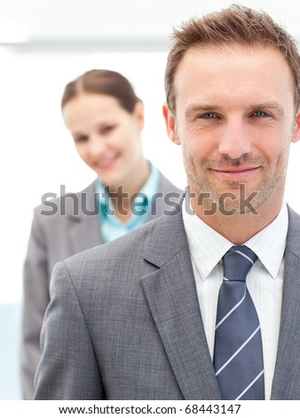 Confident businesswoman and businessman posing together in line at work - stock photo