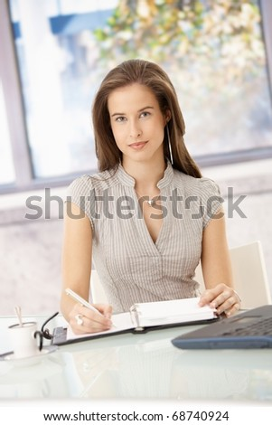 Confident businesswoman at work, taking notes to calendar, looking at camera, smiling.? - stock photo