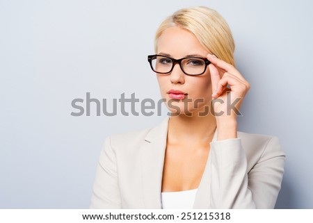 Confident businesswoman. Confident young businesswoman adjusting her eyewear and looking at camera while standing against grey background - stock photo