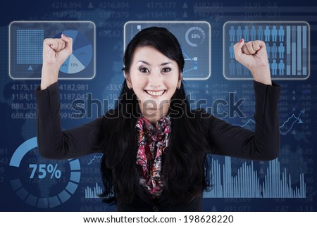 Confident businesswoman expressing success in front of modern futuristic interface - stock photo