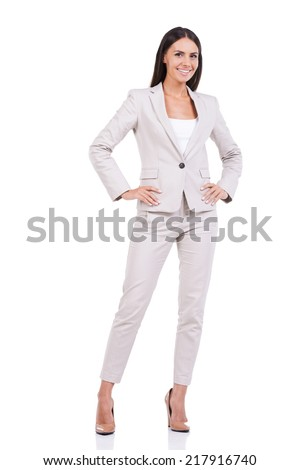 Confident businesswoman. Full length of confident young businesswoman in suit holding hands on hip and smiling while standing against white background - stock photo