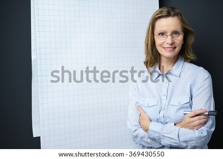 Confident businesswoman giving a presentation standing beside a blank flip chart with folded arms smiling at the camera