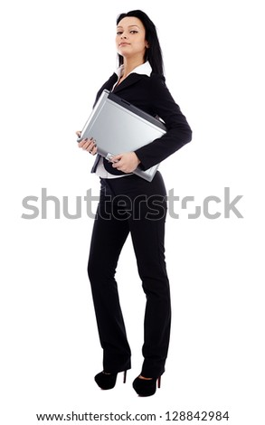 Confident businesswoman holding a laptop under her arm in full length pose isolated on white background. Business concept - stock photo