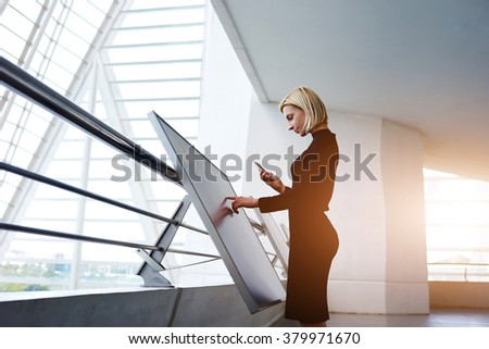 Confident businesswoman holding cell telephone while type information on modern advanced technology, young blonde female waiting for a call on mobile phone while use big touch screen computer  - stock photo