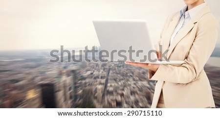 Confident businesswoman holding laptop against new york - stock photo