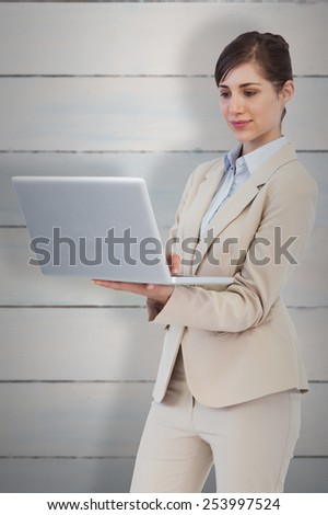 Confident businesswoman holding laptop against wooden planks - stock photo