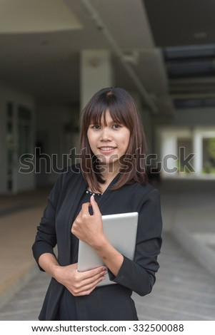 Confident businesswoman holding tablet PC outside office