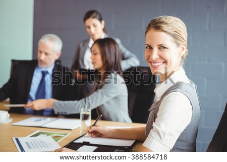 Confident businesswoman in business meeting in conference room at office - stock photo