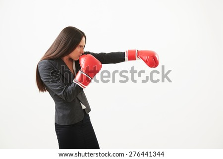 confident businesswoman in formal wear and red boxing gloves punching over light background - stock photo