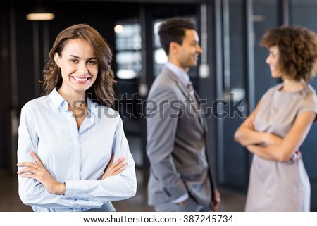 Confident businesswoman in office with his coworkers in the background - stock photo