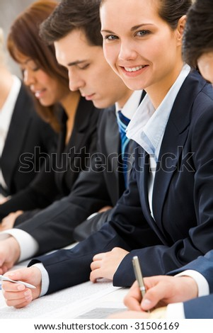 Confident businesswoman looking at camera among her colleagues at briefing