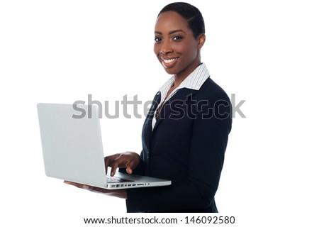 Confident businesswoman operating laptop - stock photo