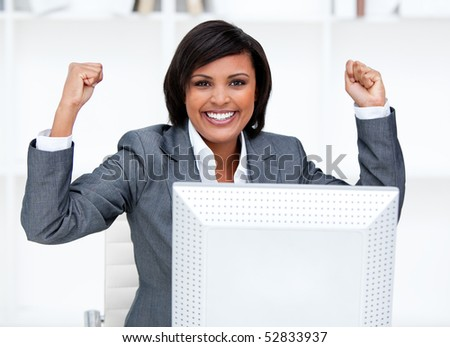 Confident businesswoman punching the air in celebration in the office