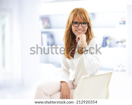 Confident businesswoman sitting at desk in office. Business people.  - stock photo