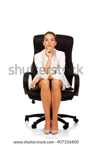 Confident businesswoman sitting on armchair - stock photo