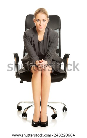 Confident businesswoman sitting on armchair, looking at the camera. - stock photo