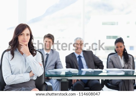Confident businesswoman sitting with her hand on her chin in front of her serious team