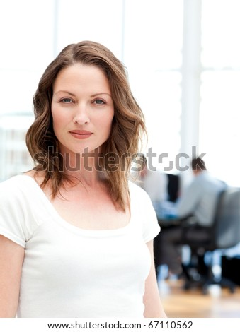 Confident businesswoman standing in front of her team while working at a table - stock photo