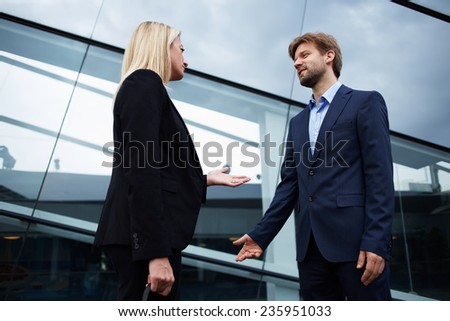 Confident businesswoman talking with his colleague standing near office building, business professionals having a discussion, office people talking about the work standing near skyscraper