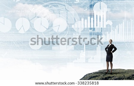 Confident businesswoman with arms on waist standing on top