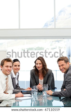 Confident businesswoman with herteam at a table during a meeting - stock photo