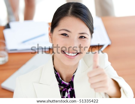 Confident businesswoman with thumbs up at work - stock photo