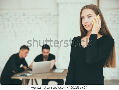 Confident businesswoman. Young woman holding mobile phone while his colleagues discussing something in the background