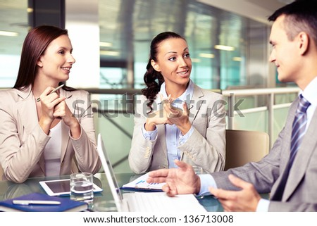 Confident businesswomen looking at their boss at meeting while sharing ideas - stock photo