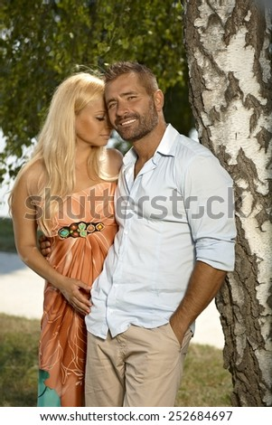 Confident casual caucasian man with pretty blonde girlfriend outdoors. Leaning against tree, smiling. hands in pocket.