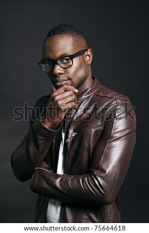 Confident casual young black man wearing brown leather jacket and glasses. Studio portrait against dark background. - stock photo