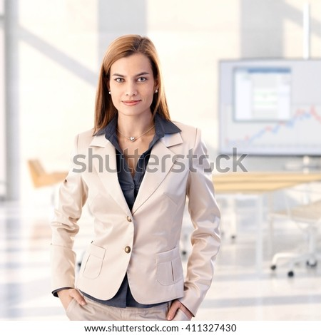 Confident caucasian blonde young businesswoman standing at bright office, smiling, looking at camera, hands in pocket, woman suit, copyspace. - stock photo