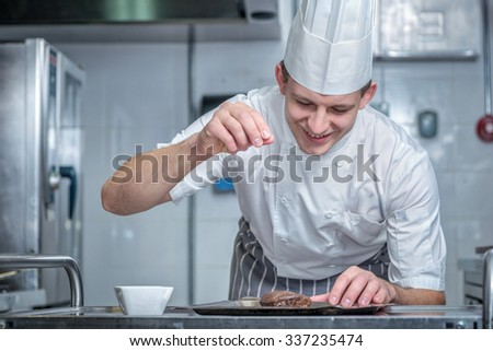 Confident chef adds spice to the meat. Young chef preparing a delicious meal in the kitchen of the restaurant. - stock photo