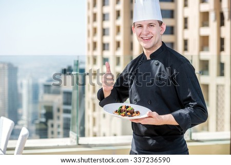 Confident chef holding a plate in his hands and smiling directly at the camera. Cheerful chef standing in a restaurant, and show a thumbs up - stock photo