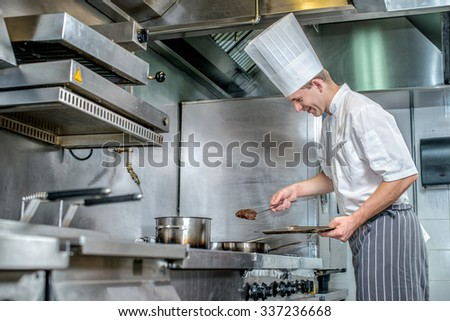 Confident chef keeps the meat to the pan. Young chef preparing a delicious meal in a restaurant kitchen near the stove and looking at the camera - stock photo