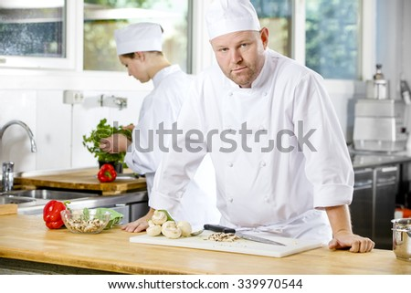 Confident chef making food in large kitchen - stock photo