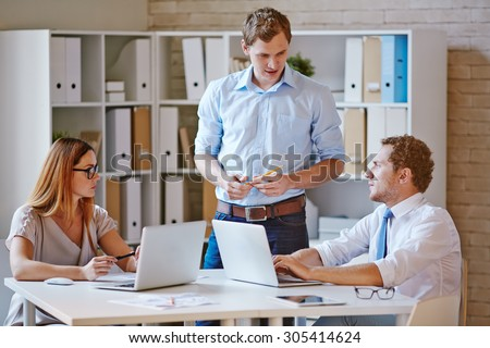 Confident co-workers discussing plans in office