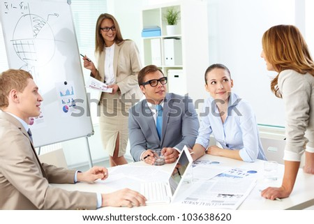 Confident co-workers listening to top manager explanation of her strategy at meeting - stock photo
